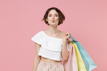 Funny young woman girl in summer clothes hold package bag with purchases isolated on pink background studio portrait. Shopping discount sale concept. Mock up copy space. Blowing lips making duck face.