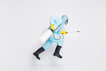 Full body profile side photo man jump run hurry disinfect covid spread house wear white hazmat suit...