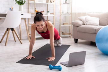 Personal trainer giving online workout class via laptop at home, doing plank or push ups