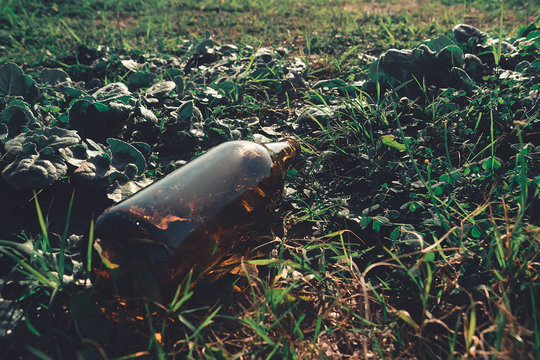 Glass bottle littering a field. Possible fire hazard, Concept image on how sun rays can make a fire through a crystal. Rubbish is dangerous for the ecosystem. Leave no trace behind.