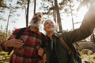 Active happy senior couple hiking together in forest and exloring nature