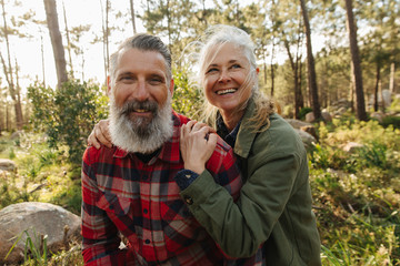 Portrait of happy smiling senior couple on hike in forest