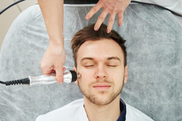 Beautician woman does the anti-aging procedure of rf face skin lifting for a young man in a beauty parlor close up