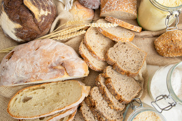 Top view of wheat and rye whole grain loafs and baguettes cut in slices, corn flour in jar and ears. Bakery or traditional bread concept