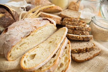Closeup of wheat and whole grain slices, cut loafs and baguettes, sackcloth and flour in jar. Bakery or traditional bread concept