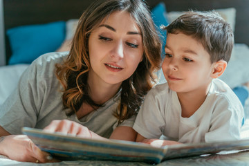 selective focus of attractive mother and happy toddler boy looking at book