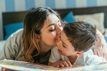 attractive mother kissing cheek of cute toddler boy at home