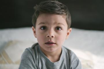 adorable toddler boy looking at camera at home