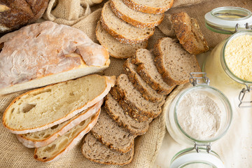 Freshly baked traditional wheat and whole grain baguettes cut in slices, burlap sackcloth and flour in jar. Top view. Bakery or traditional bread concept