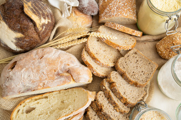 Table with wheat and rye whole grain loafs and baguettes cut in slices, corn flour in jar and ears. Top view. Bakery or traditional bread concept