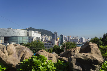 view on a cityscape of Busan from park with decorative rocks