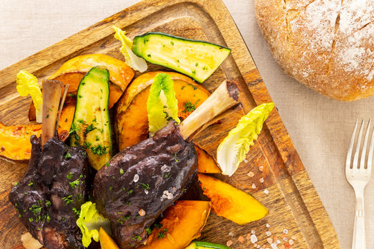 Glazed braised lamb shank with pumpkin and zucchini on a chopping board on a beige tablecloth aside a fork and a bread loaf. Flat lay top view.