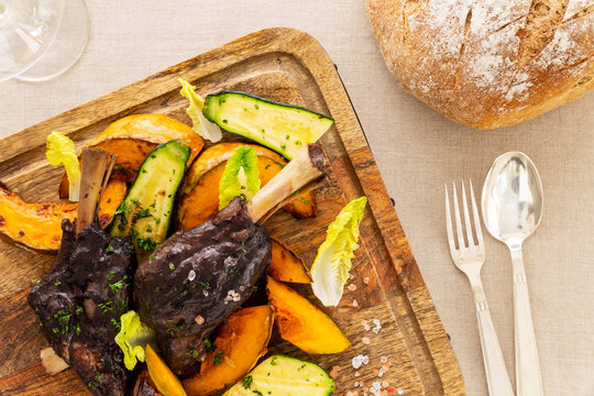 Glazed braised lamb shank with pumpkin and zucchini on a chopping board on a beige tablecloth aside a fork, a spoon, a bread loaf and a wine glass. Flat lay top view.