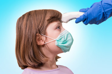 coronavirus epidemic outbreak concept:Pediatrician or doctor checks elementary age girl's body temperature using infrared forehead thermometer (thermometer gun) for virus symptom -