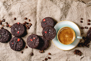 Homemade dark chocolate salted brownies cookies decorated by dried raspberries, with salt flakes, coffee beans, mint and cup of coffee over rag cloth background. Flat lay, space