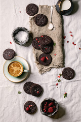 Homemade dark chocolate salted brownies cookies decorated by dried and fresh raspberries, with salt flakes, berries, mint, milk and cup of coffee over white cotton cloth. Flat lay, space