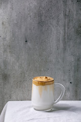 Dalgona frothy coffee trend korean drink milk latte with coffee foam in glass mug standing on white cotton table cloth. Copy space
