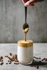 Dalgona frothy coffee trend korean drink milk latte with coffee foam in glass mug, foam flowing from spoon. Gray texture table. Copy space