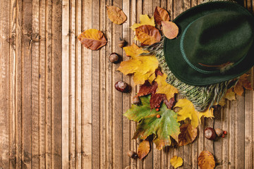 Felt hat and knitted green scarf on variety of red and yellow autumn leaves and chestnuts over wooden plank background. Flat lay. Fall creative background.