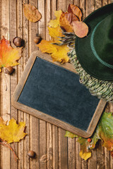 Felt hat, knitted green scarf, vintage black empty chalkboard on variety of red and yellow autumn leaves and chestnuts over wooden plank background. Flat lay. Fall creative background.