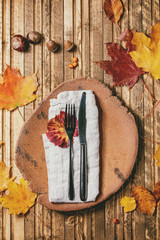 Empty ceramic plate with textile napkin and cutlery on variety of red and yellow autumn leaves over wooden plank background. Flat lay. Fall food background.