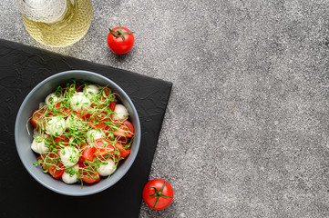 Italian food. Delicious caprese salad with mozzarella cheese, cherry tomatoes and arugula microgreens. Top view with copy space. Gray stone background.