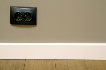 Close up of white plastic plinths on dark wooden oak floor parquet and black electric socket...