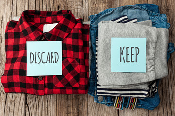 Stack of old clothes to discard (declutter) or keep. Recycle clothes, eco cotton.