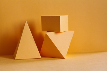 Yellow geometrical platonic solids figures still life composition, simplicity concept. Three-dimensional prism pyramid rectangular cube objects on yellow background.