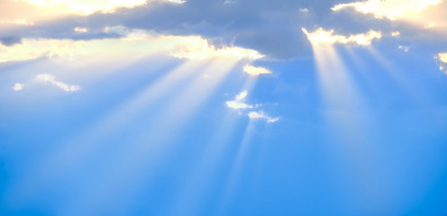 The sun's rays break through the blue clouds. The background of the sky.