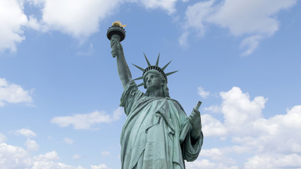 Statue of Liberty in New York City with blue sky and clouds behind.