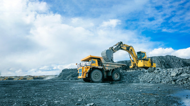 Work of trucks and the excavator in an open pit