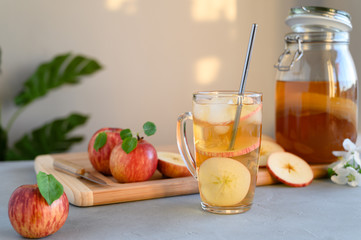 Homemade fermented kombucha or cider with apple slices and ice in a glass. A healthy probiotic refreshing non-alcoholic cocktail. Horizontal orientation with copy space.
