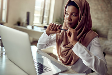 Pensive Muslim businesswoman working on laptop at her office desk.
