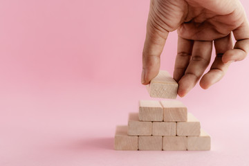 Hand putting the wooden toy on pink background for leisure activities concept
