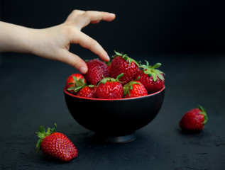 Child's hand taking a strawberry from a bowl