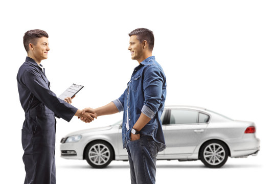 Man taking car to an auto repair shop and shaking hands with auto mechanic worker