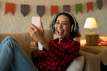 Cheerful african american woman with headphone smiling with broad smile and using mobile phone Indoors at home living room. Party, weekend, dance, quarantine, concert, music concept.