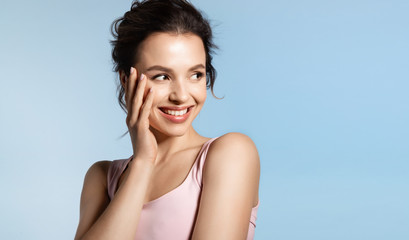 Young woman with bare shoulder and shiny glowing perfect face skin laughing timid.