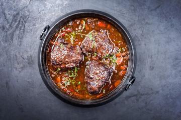 Traditionelle deutsche geschmorte Ochsenbäckchen vom Rind in brauner Rotwein Sauce mit Karotten und Zwiebel angeboten als Draufsicht in einem Modern Design Schmortopf auf einem rustikalen Board