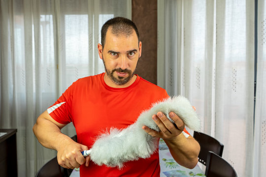 Man with a beard and short hair in a red shirt with a feather duster to clean the pole in the living room at home