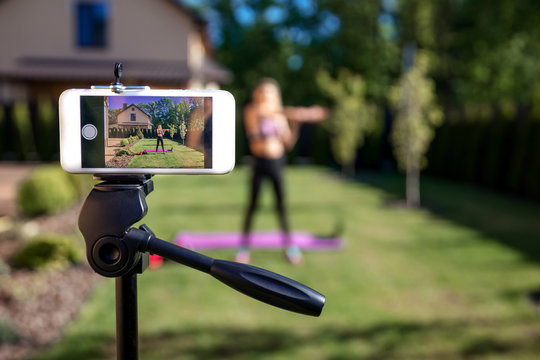 Sportive fitness coach woman recording video blog  by phone about  workout  training at the garden with fresh green grass near house.