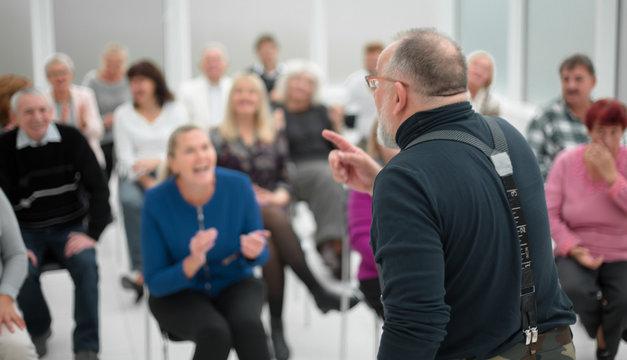 Mature caucasian man gives a speech in meeting in modern open office