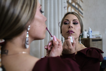 young woman puts on makeup in the bathroom while looking in the mirror