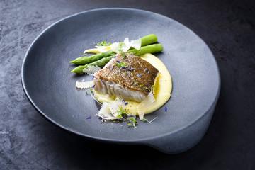 Traditionelles gebratenes Skrei Kabeljau Fisch Filet mit grünen Spargel Spitzen und Kartoffelpüree Creme in Parmesan Oliven Öl Sauce als closeup auf einem Modern Design Teller mit Textfreiraum