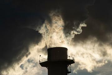 Smoke stack emitting smoke during sunrise