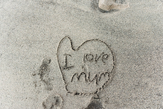 Child's drawing in sand of heart with I love mum written inside