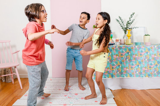Siblings dancing and playing confetti during Easter home party