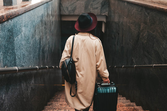 Stylish woman with a suitcase get down the stairs of the train station