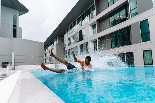 Young boy jumping and falling into a pool